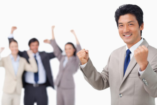 A man celebrates his raise as his coworkers cheer in the background.
