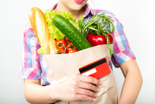 A vegan holds a bag of fruits and vegetables in her arms and a credit card in her hand.