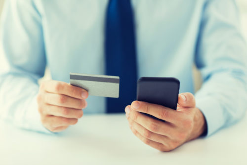 A close up of a man with a credit card in one hand and a smartphone being used for mobile banking in the other.