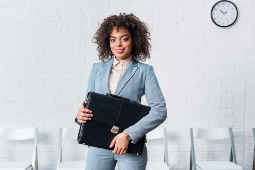 A c-level executive holding her briefcase.