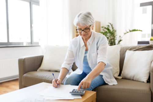 An elderly woman calculating her annuity with a calculator on her couch.