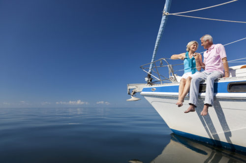 A retired couple sitting in the front of a sailboat.