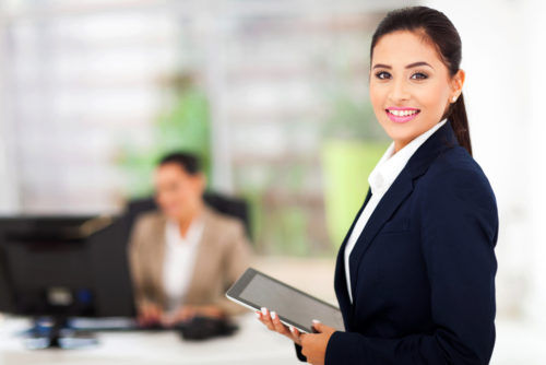 An executive assistant holds a tablet and smiles at the camera while her colleague works in the background.