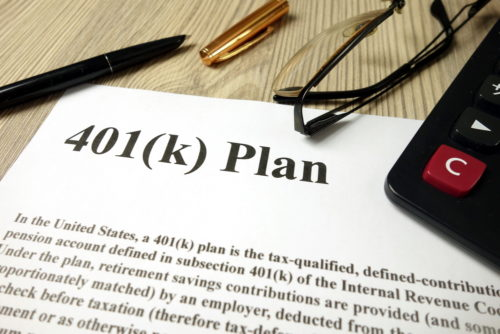 """A calculator, pen, and glasses sit on top of a document labeled """"401(k) plan."""""""