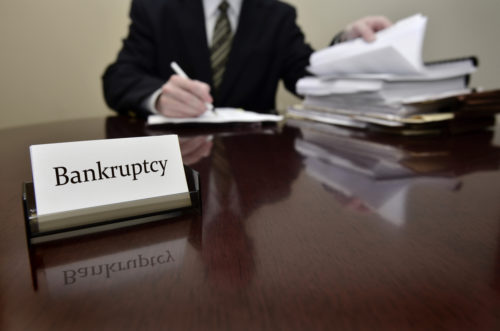 A bankruptcy accountant sitting at a desk with files and papers.