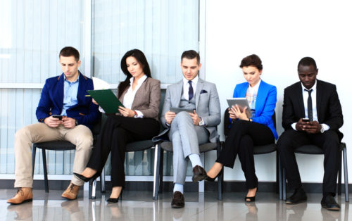 5 prospective employees sit next to each other, waiting for a job interview.