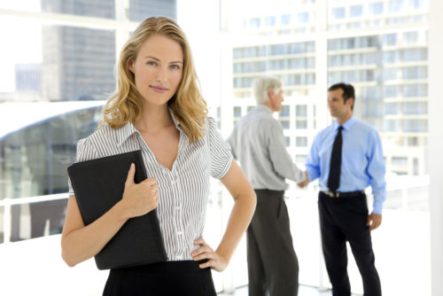 A sales manager stands in front of her employee, who is greeting a customer.