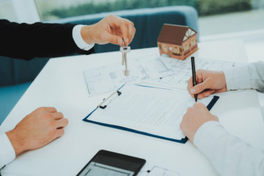 A man signing a contract while another man is handing a set of keys ti him across a table.