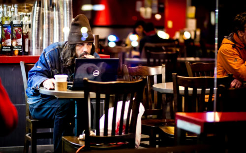 An unemployed man looking for jobs on his laptop in a New York cafe.