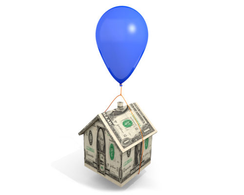 A conceptual image of a balloon tied to a tiny model house made out of money.