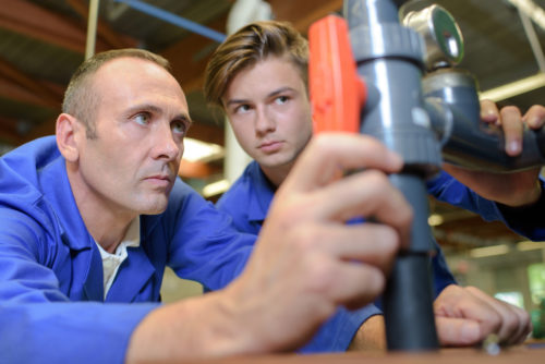 A professor and student working on piping at a trade school.
