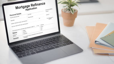 A laptop's screen is open to a mortgage refinance application.