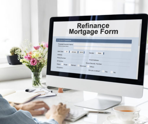 A woman sitting at a computer, whose screen displays a mortgage refinance form.