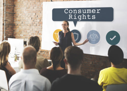 """A woman speaking to an audience in front of a screen that reads """"consumer rights."""""""