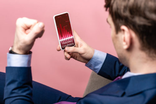 A businessman sits in a pink room while trading stocks on his phone, with a fist raised in the air in excitement.