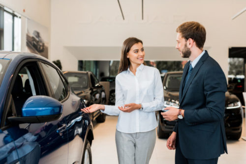 A car dealer showing a man around in a showroom.