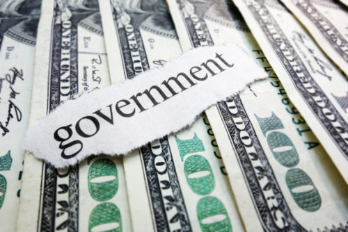 """100 dollar bills fanned out under a torn out label that reads """"government."""""""