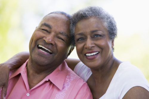 A retired couple hugging and smiling.