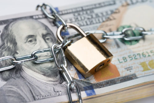 A stack of $100 bills is chained and locked up.