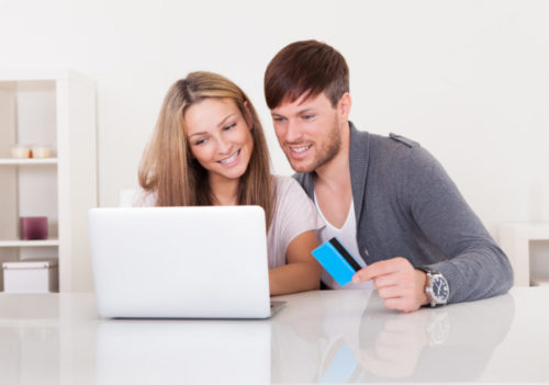 A smiling couple using their laptop, while the male holds a credit card.