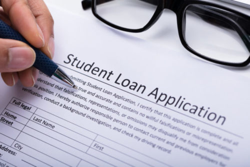 A close up of a person's hand filling out a student loan application.