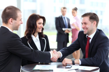 A couple of bank representatives greeting a client.