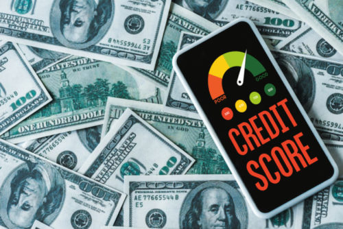 A smartphone displaying a credit score gauge lies on top of $100 bills.