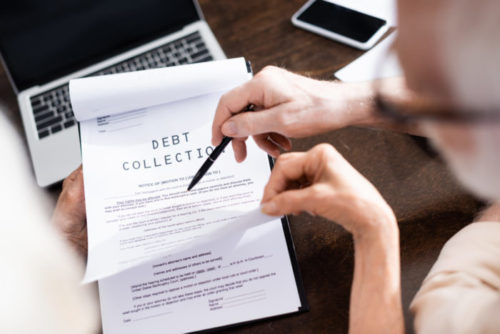 """A person pointing to a document labeled """"debt collection"""" with a pen."""