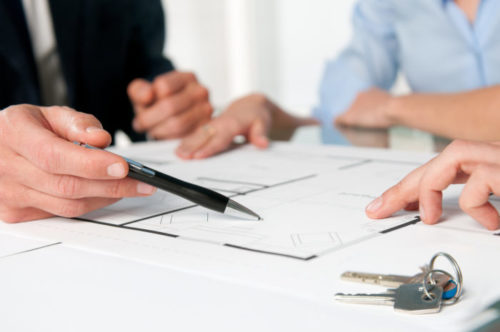 A closeup of a mortgage broker pointing to a document with a pen, showing his client couple a clause in the mortgage.