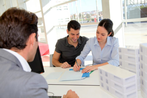 An insurance agent watches a smiling couple sign a document.