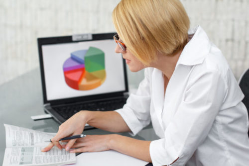 A woman looking over financial documents, while a chart is displayed on her computer.