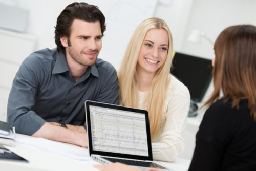 An insurance agent sharing financial figures from her computer screen to a smiling couple.