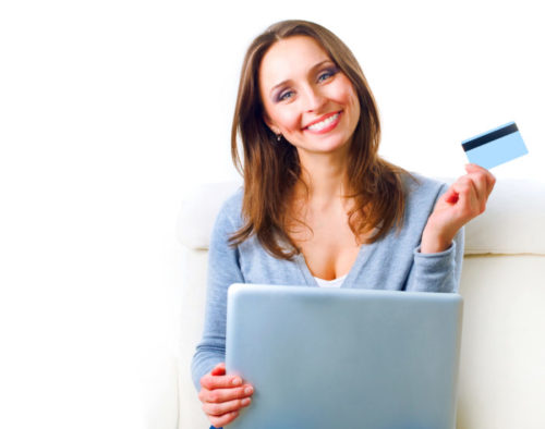A smiling woman shops online while holding a credit card.