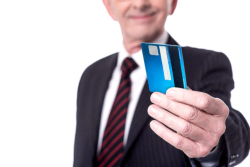 A person in business attire extends a credit card toward the camera.