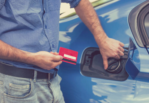 A man holding a credit card while opening the fuel tank of his car.
