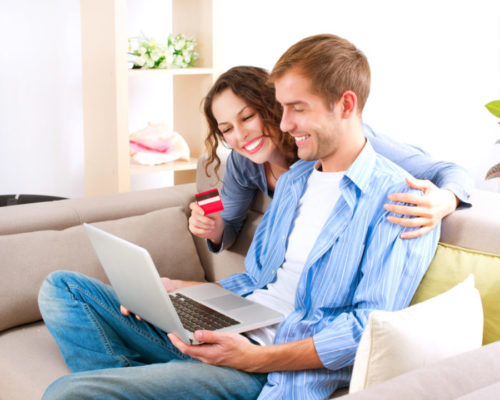 A smiling couple using their credit card to shop online.