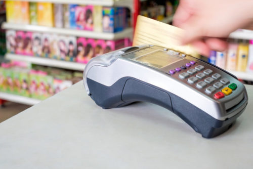 A credit card being swiped through a payment terminal at a supermarket.