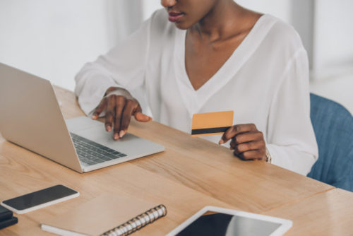 A woman using her computer while holding her credit card.
