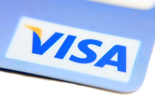 A closeup of the corner of a credit card shows the Visa logo.