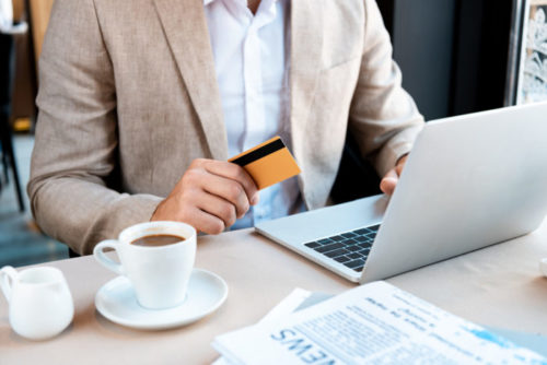 A person in business attire working on their laptop readies his credit card to pay at a cafe.