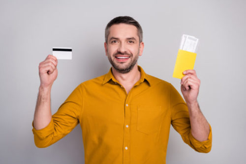 A smiling man holds plane tickets in one hand and a credit card in the other.