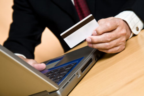 A person in business attire shopping on their laptop while holding a credit card.
