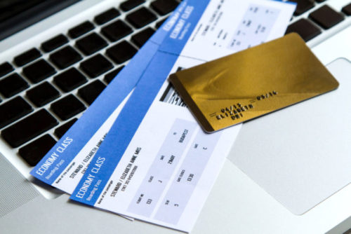 A credit card sits on a laptop keyboard alongside two plane tickets.