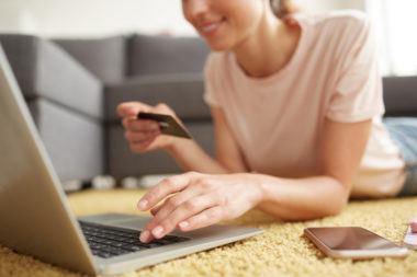 A smiling person lying down, typing on a laptop while holding a credit card.