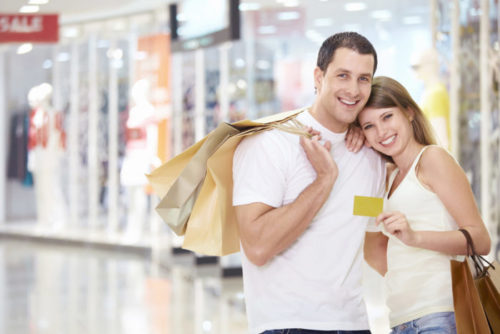 One person of a smiling couple holds a credit card while the other holds several shopping bags.