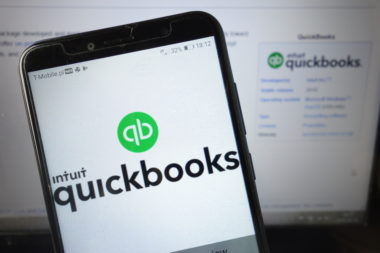 Both a phone and a computer screen display the QuickBooks website.
