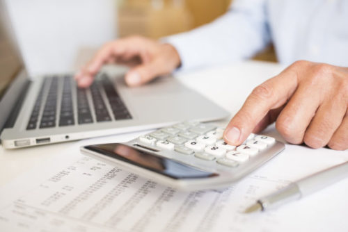 A person typing on a computer while tallying financial figures on a calculator.