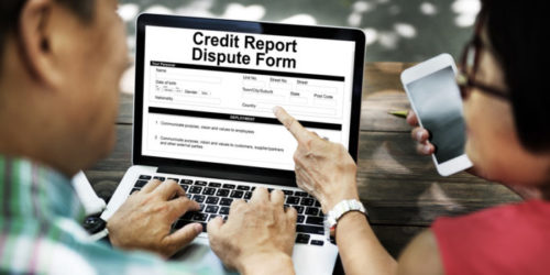 """Two people looking at a computer screen that reads """"credit report dispute form."""""""
