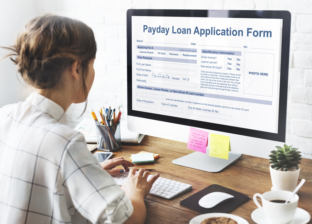 A person filling out a payday loan application form on their computer.
