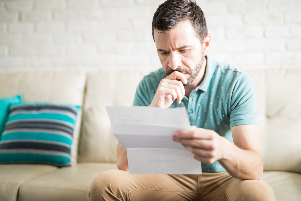A person looks worried as they read some financial documents.